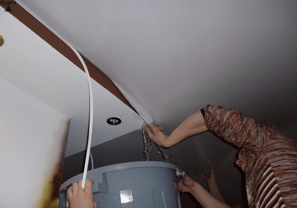 Слив воды натяжного потолка через край полотнища